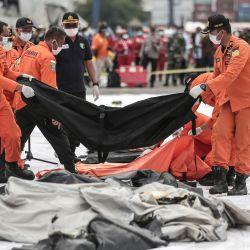 Los equipos de rescate colocan bolsas para cadáveres que contienen restos humanos recuperados del lugar del accidente del vuelo SJ182 de Sriwijaya Air en el puerto de Yakarta, luego del accidente del avión Boeing 737-500 de la aerolínea en el mar de Java minutos después del despegue. | Foto:Aditya Aji / AFP