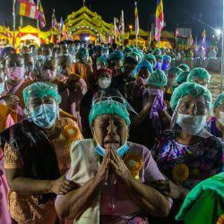 Los devotos lloran mientras se reúnen para presentar sus respetos durante la cremación del monje Wai Bu La en Thanlyin, Yangon, donde cientos de devotos presentaron sus respetos finales en una ceremonia fúnebre demorada por la propagación del Coronavirus Covid-19 después de que el monje falleciera hace unos ocho meses. | Foto:Sai Aung Main / AFP