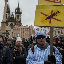 Un manifestante vestido con un traje de prisionero sostiene una pancarta con la palabra  | Foto:Michal Cizek / AFP