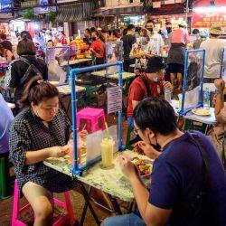 Las personas cenan separadas por pantallas divisorias en una esquina de comida callejera en el barrio chino de Bangkok, después de que las autoridades tailandesas impusieran restricciones a los restaurantes debido al reciente brote de coronavirus Covid-19. | Foto:Mladen Antonov / AFP