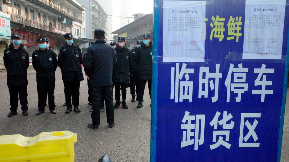 This file photo taken on January 12, 2020, shows security guards standing in front of the closed Huanan wholesale seafood market, in the city of Wuhan, Hubei province, China. January 11, 2021 marks the anniversary of China confirming its first death from the Covid-19 coronavirus -- a 61-year-old man who was a regular at the now-notorious Wuhan wet market linked to many of the early cases. (FILES) This file photo taken on January 12, 2020 shows security guards standing in front of the closed Huanan wholesale seafood market, where health authorities say a man who died from a respiratory illness had purchased goods from, in the city of Wuhan, Hubei province.