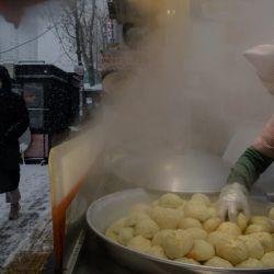 Un vendedor prepara bolas de masa en un puesto a la entrada de un mercado callejero durante una nevada en Seúl. | Foto:Ed Jones / AFP