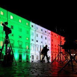 Una vista en Roma muestra a periodistas en video que trabajan fuera del Palazzo Chigi, la sede del gobierno italiano, iluminados con los colores de la bandera italiana, ya que se espera que el gobierno de Italia discuta más tarde una recuperación del coronavirus de 220 mil millones de euros. paquete de gastos. | Foto:Vincenzo Pinto / AFP