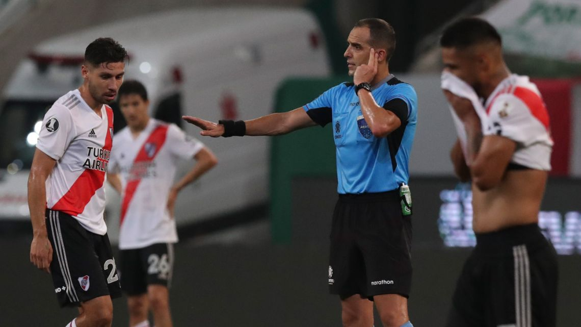 Uruguayan referee Esteban Ostojich consults the VAR as he conducts the Copa Libertadores semifinal football match between Brazil's Palmeiras and Argentina's River Plate at the Allianz Parque stadium in São Paulo, Brazil, on January 12, 2021.