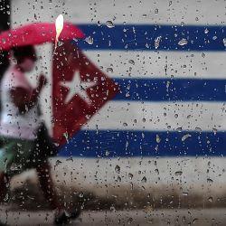 Una mujer camina cerca de un grafiti con la bandera cubana en La Habana. - El ministro de Relaciones Exteriores de Cuba, Bruno Rodríguez, criticó el lunes a la administración del presidente de Estados Unidos, Donald Trump, por  | Foto:Yamil Lage / AFP