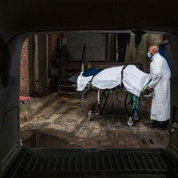 El transportista de Maryland Cremation Services, Reggie Elliott, lleva los restos de una víctima de Covid-19 a su camioneta desde la morgue del hospital en Baltimore, Maryland, durante la pandemia de Covid-19. | Foto:Andrew Caballero-Reynolds / AFP