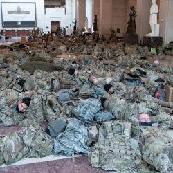 Los miembros de la Guardia Nacional descansan en el Centro de Visitantes del Capitolio en el Capitolio en Washington, DC, antes de una votación esperada en la Cámara para acusar al presidente estadounidense Donald Trump. | Foto:Saul Loeb / AFP