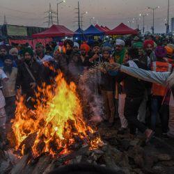 Los agricultores que protestan celebran el festival de Lohri alrededor de una hoguera, mientras continúan su protesta a lo largo de una carretera bloqueada contra las recientes reformas agrícolas del gobierno central, en la frontera estatal de Gazipur Delhi-Uttar Pradesh, en Ghaziabad. | Foto:Prakash Singh / AFP