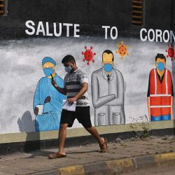 Un peatón pasa junto a un mural pintado para agradecer a los trabajadores de primera línea de diversas profesiones que luchan contra la propagación del coronavirus Covid-19, en Mumbai. | Foto:Indranil Mukherjee / AFP