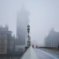 Los peatones cruzan el puente de Westminster mientras la niebla envuelve la Torre Elizabeth, comúnmente conocida con el nombre de la campana,  | Foto:Tolga Akmen / AFP