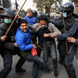 Manifestantes de la Unión de Estudiantes de Nepal, afiliada al partido opositor del Congreso, se pelean con la policía durante una manifestación contra la disolución del parlamento del país en Katmandú. | Foto:Prakash Mathema / AFP