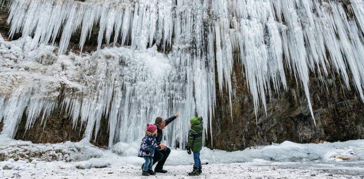 Austria, Rankweil: Se ve a excursionistas de invierno de pie frente a una pared de hielo que se ha formado en un desfiladero.