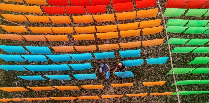 En esta foto aérea, los trabajadores secan la tela después de un proceso de teñido en una fábrica en Araihazar, a unos 50 km de Dhaka.