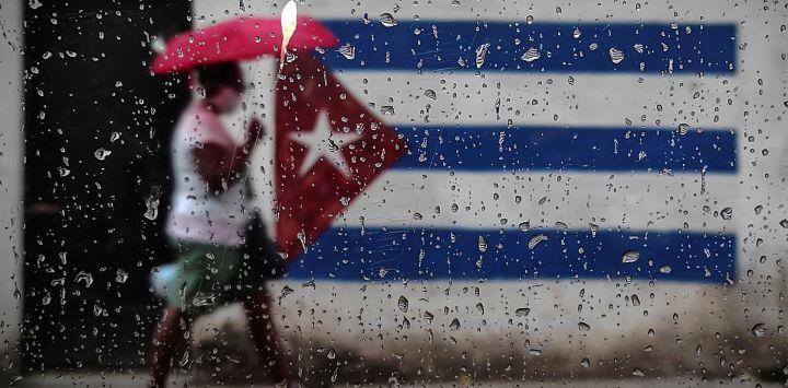 Una mujer camina cerca de un grafiti con la bandera cubana en La Habana. - El ministro de Relaciones Exteriores de Cuba, Bruno Rodríguez, criticó el lunes a la administración del presidente de Estados Unidos, Donald Trump, por