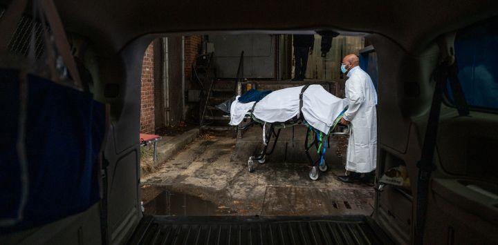El transportista de Maryland Cremation Services, Reggie Elliott, lleva los restos de una víctima de Covid-19 a su camioneta desde la morgue del hospital en Baltimore, Maryland, durante la pandemia de Covid-19.