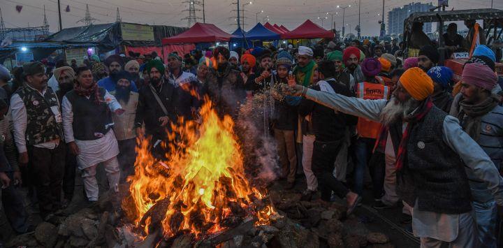 Los agricultores que protestan celebran el festival de Lohri alrededor de una hoguera, mientras continúan su protesta a lo largo de una carretera bloqueada contra las recientes reformas agrícolas del gobierno central, en la frontera estatal de Gazipur Delhi-Uttar Pradesh, en Ghaziabad.
