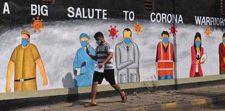 Un peatón pasa junto a un mural pintado para agradecer a los trabajadores de primera línea de diversas profesiones que luchan contra la propagación del coronavirus Covid-19, en Mumbai.