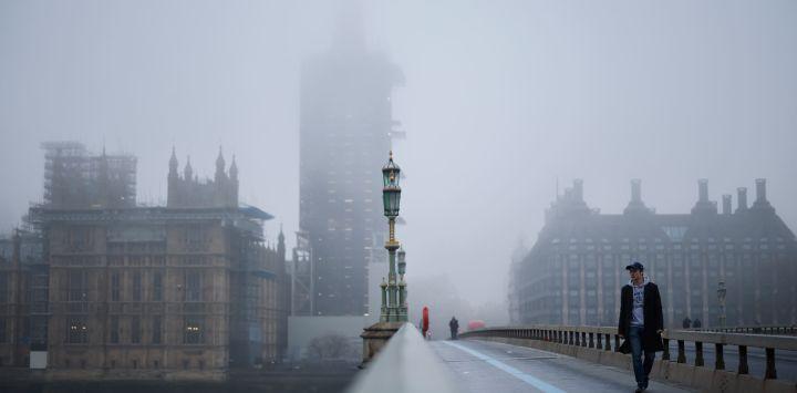 Los peatones cruzan el puente de Westminster mientras la niebla envuelve la Torre Elizabeth, comúnmente conocida con el nombre de la campana,