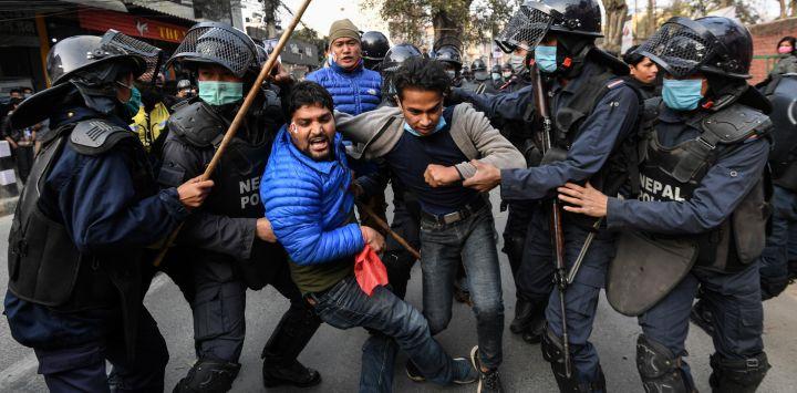 Manifestantes de la Unión de Estudiantes de Nepal, afiliada al partido opositor del Congreso, se pelean con la policía durante una manifestación contra la disolución del parlamento del país en Katmandú.