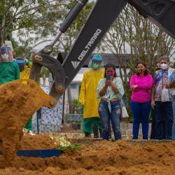 Se utiliza una retroexcavadora para enterrar a una víctima de COVID-19 junto a sepultureros y familiares en el cementerio de Nossa Senhora Aparecida en Manaus, estado de Amazonas, Brasil, en medio de la pandemia del nuevo coronavirus. | Foto:Michael Dantas / AFP