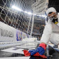 Un trabajador de saneamiento desinfecta el área de portería antes del partido del Campeonato Mundial Masculino de Balonmano 2021 entre los equipos del Grupo D de Dinamarca y Baréin en el Palacio de Deportes del Estadio de El Cairo en la capital egipcia. | Foto:Mohamed Abd El Ghany / POOL / AFP