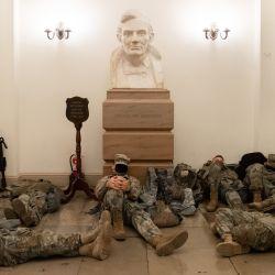 Los miembros de la Guardia Nacional descansan en la Rotonda del Capitolio de los EE. UU. En Washington, DC, antes de una votación esperada de la Cámara para acusar al presidente de los EE. UU., Donald Trump. | Foto:Saul Loeb / AFP