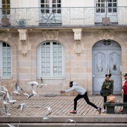 Un hombre ahuyenta a las gaviotas mientras él y sus amigos se preparan para comer en un banco porque los restaurantes están cerrados debido a la pandemia de Covid-19 en la ciudad de Nantes. | Foto:Loic Venance / AFP