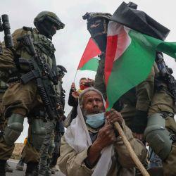 Soldados israelíes arrestan a un anciano palestino que participaba en una manifestación junto a manifestantes de izquierda israelíes contra los asentamientos y la confiscación de tierras, cerca de la aldea de Yatta al sur de la ciudad de Hebrón en la ocupada Cisjordania. | Foto:Hazem Bader / AFP