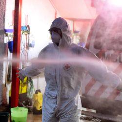 Paramédico de la Cruz Roja Mexicana Humberto Xoyatla es higienizado luego de haber trasladado a un paciente positivo a COVID-19 a una sala de emergencias en Toluca, México. | Foto:Alfredo Estrella / AFP