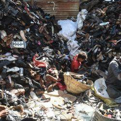 Los trabajadores desmantelan zapatos viejos para reciclarlos en un taller en Karachi. | Foto:Rizwan Tabassum / AFP