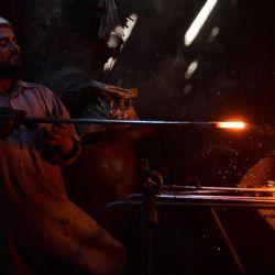 Un trabajador trabaja en una pequeña fábrica de hierro en Karachi. | Foto:Asif Hassan / AFP