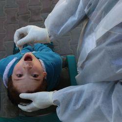 Territorios palestinos, Deir Al-Balah: un trabajador médico que usa equipo de protección personal (EPP) toma una muestra de hisopado nasal de un niño durante la prueba de detección del coronavirus (Covid-19) dentro de una mezquita. | Foto:Ashraf Amra / APA Imágenes a través de ZUMA Wire / DPA