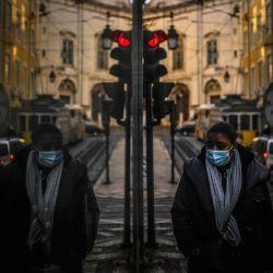 Una mujer que usa una máscara facial se refleja en un escaparate mientras caminaba en Lisboa cuando Portugal ingresó a un nuevo bloqueo por un aumento en los casos de coronavirus. | Foto:Patricia De Melo Moreira / AFP