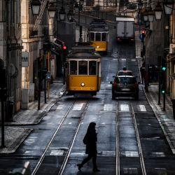 Una mujer cruza una calle pasando tranvías en Lisboa cuando Portugal ingresó a un nuevo bloqueo por un aumento en los casos de coronavirus. | Foto:Patricia De Melo Moreira / AFP
