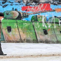 Un hombre que usa una mascarilla para protegerse contra la enfermedad del coronavirus pasa junto a un graffiti en la ciudad de Klimovsk, a unos 40 km de Moscú. | Foto:Yuri Kadobnov / AFP