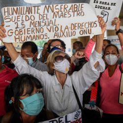 Maestros venezolanos gritan consignas durante una manifestación exigiendo al gobierno mejoras salariales en el Día del Maestro frente al Ministerio de Trabajo, en Caracas. | Foto:Federico Parra / AFP