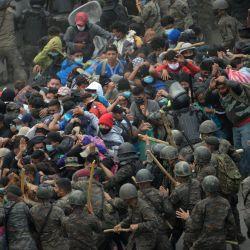Migrantes hondureños, parte de una caravana que se dirige a los Estados Unidos, chocan con las fuerzas de seguridad guatemaltecas en Vado Hondo, Guatemala.   Foto:Johan Ordonez / AFP