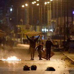 Los manifestantes bloquean una calle durante los enfrentamientos con las fuerzas de seguridad en el suburbio de la ciudad de Ettadhamen, en las afueras del noroeste de Túnez, la capital de Túnez, en medio de una ola de protestas nocturnas en el país del norte de África.   Foto:Fethi Belaid / AFP