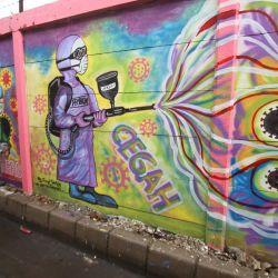 Un artista local pinta un mural en una pared a lo largo de una calle en medio de la pandemia del coronavirus Covid-19 en Tangerang. | Foto:Demy Sanjaya / AFP