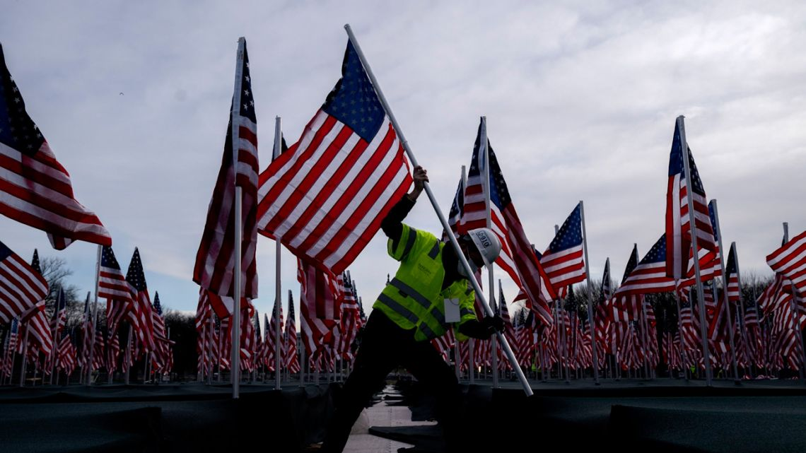 A worker plants an American flag along the National Mall in Washington DC on January 18, 2021.