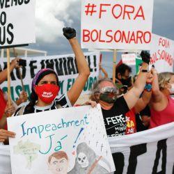Manifestantes realizan una protesta contra las medidas del presidente de Brasil, Jair Bolsonaro, para enfrentar la pandemia del coronavirus COVID-19, frente al palacio presidencial de Planalto, en Brasilia, Brasil. | Foto:Sergio Lima / AFP