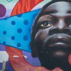 Una mujer con mascarilla se para junto a un mural callejero en Bogotá. - Bogotá entrará en confinamiento total el próximo fin de semana, por tercera vez consecutiva, debido al aumento de infecciones por coronavirus que mantiene a los hospitales en el Capital colombiana al borde del colapso. | Foto:Juan Barreto / AFP