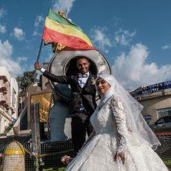 Un novio sostiene una bandera imperial etíope mientras posa con su novia para una foto tomada frente al monumento del emperador Tewodros II, en la ciudad de Gondar, Etiopía. | Foto:Eduardo Soteras / AFP