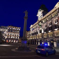 Un coche de policía patrulla frente al ayuntamiento de Trieste, durante la pandemia de COVID-19 provocada por el nuevo coronavirus. | Foto:Miguel Medina / AFP