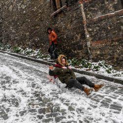Niños se deslizan en una calle nevada en el distrito de Balat de Estambul. | Foto:Ozan Kose / AFP