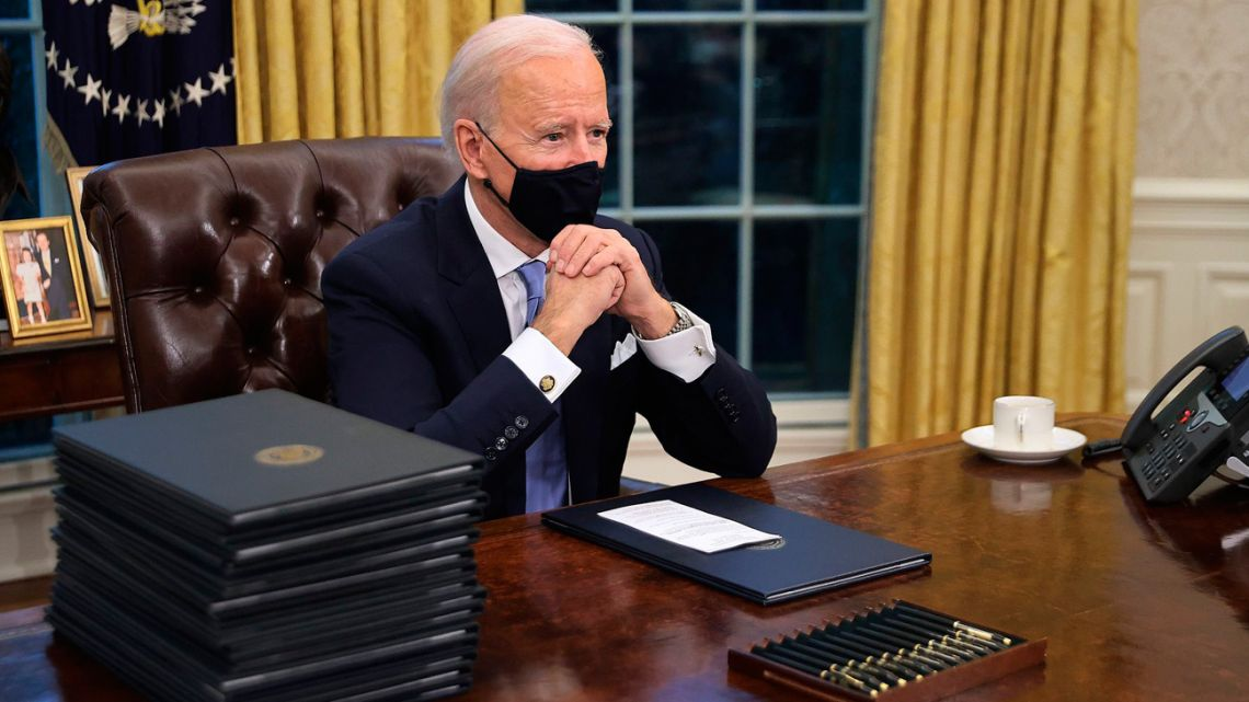 Joe Biden sits in the Oval Office at the White House after his inauguration as the 46th president of the United States of America.