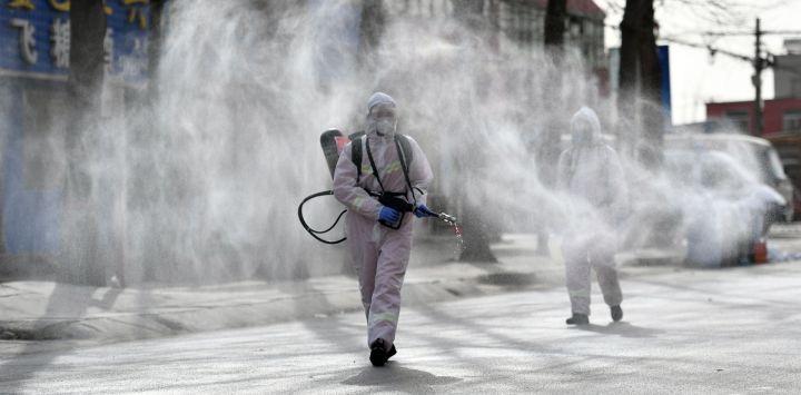 Esta foto muestra a personas con trajes protectores rociando desinfectante en una calle del distrito de Gaocheng, que fue declarada zona de alto riesgo para Covid-19 en Shijiazhuang, en la provincia de Hebei, en el norte de China.