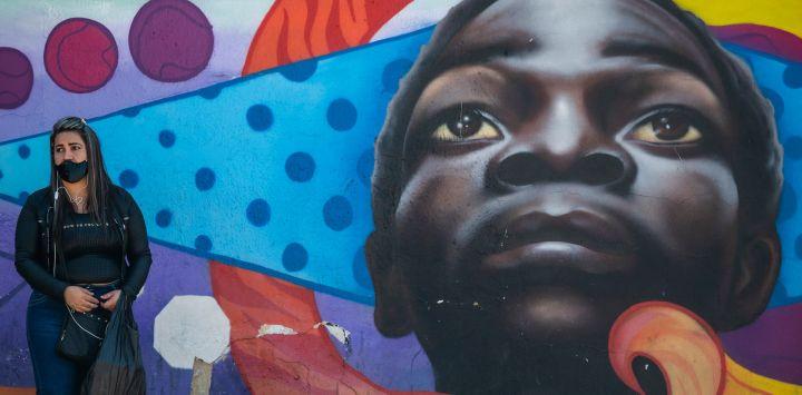 Una mujer con mascarilla se para junto a un mural callejero en Bogotá. - Bogotá entrará en confinamiento total el próximo fin de semana, por tercera vez consecutiva, debido al aumento de infecciones por coronavirus que mantiene a los hospitales en el Capital colombiana al borde del colapso.