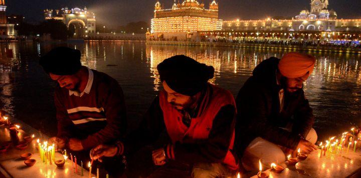 Los devotos sij encienden velas con motivo del aniversario del nacimiento del décimo gurú sij Gobind Singh, en el iluminado Templo Dorado de Amritsar.