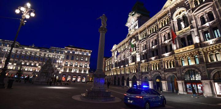 Un coche de policía patrulla frente al ayuntamiento de Trieste, durante la pandemia de COVID-19 provocada por el nuevo coronavirus.